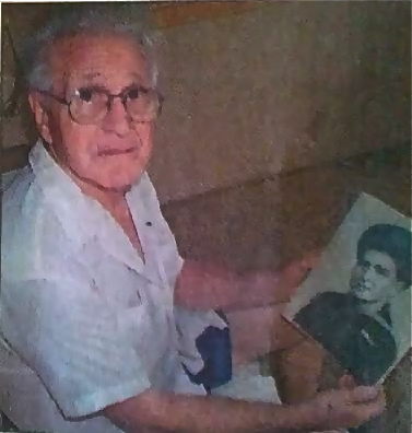 Les Thompson was a seaman aboard the destroyer Abner Reed sunk by a kamikaze at Leyte Gulf in the Philippines in October 1944.  Here he looks at a picture of himself when he served in World War I more than half a century ago. Sun photo by Don Moore
