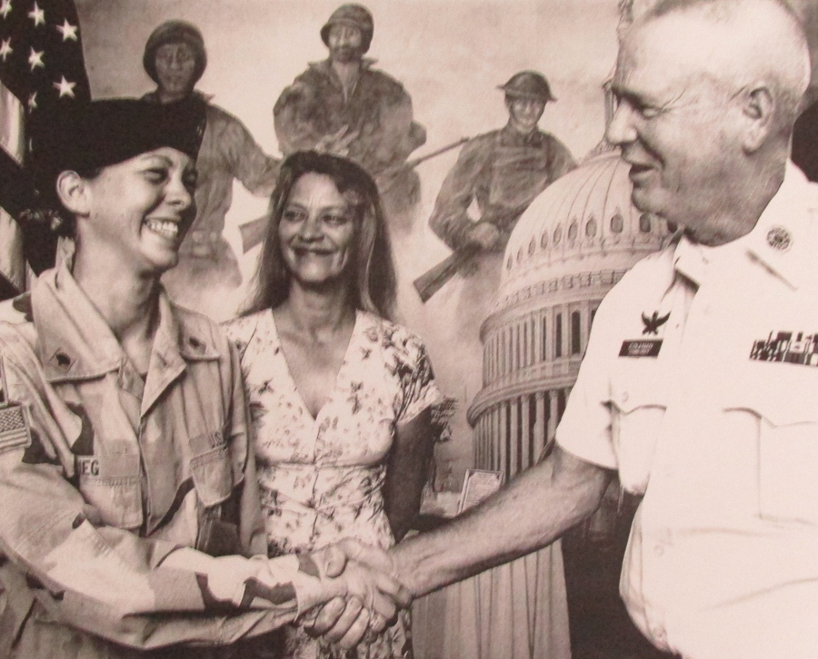 Cpl. Gwen Sieg shakes hands with Cmdr. John Coleman of American Legion Post 110 in Port Charlotte as her mother, Jacqueline Merchant, looks on. Photo provided