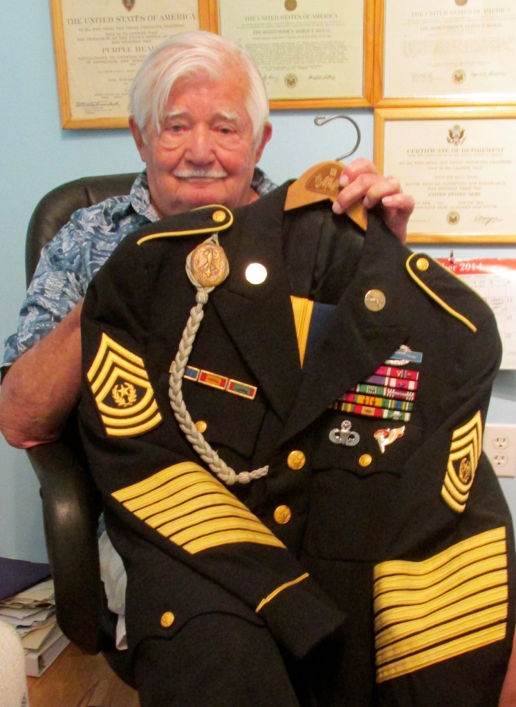 David Eshelman holds his command sergeant major's dress uniform he wore while serving as the top enlisted man in the Army. He plans to be buried in the dress uniform. Sun photo by Don Moore