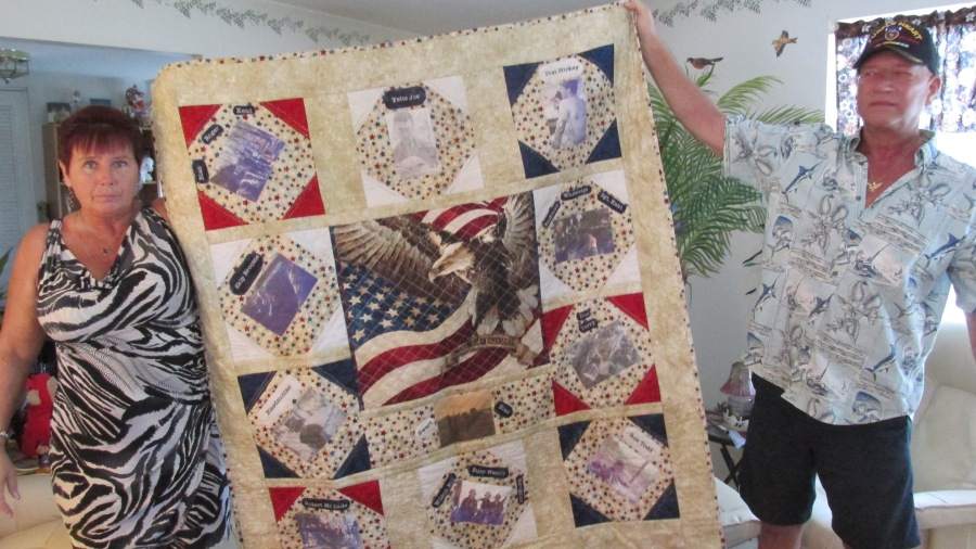 Sharon Hirkey and her husband, Donald, hold a quilt she made to be presented at a party in Rayne, La. on Veterans' Day. Each year Hirkey and a dozen of his Vietnam buddies get together twice. On Veterans' Day they meet at 'Joe's Place' in Rayne, La. and some other spot around the country. The quilt, with a picture of each of his 12 members of his fire team when they served in 'Nam, will be on display at Joe's Place watering hole for the world to see. Sun photo by Don Moore