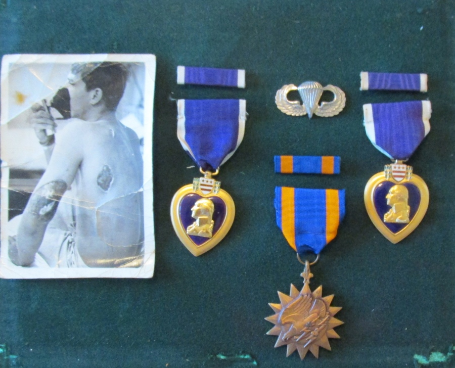 In a small shadow box on the same wall is a picture of Hirkey sitting on a hospital gurney with the bullet hole from a North Vietnam bullet plainly visible in his back an left arm. Two Purple Hearts, Airborne Wings, and the Air Medal are also displayed. Sun photo by Don Moore