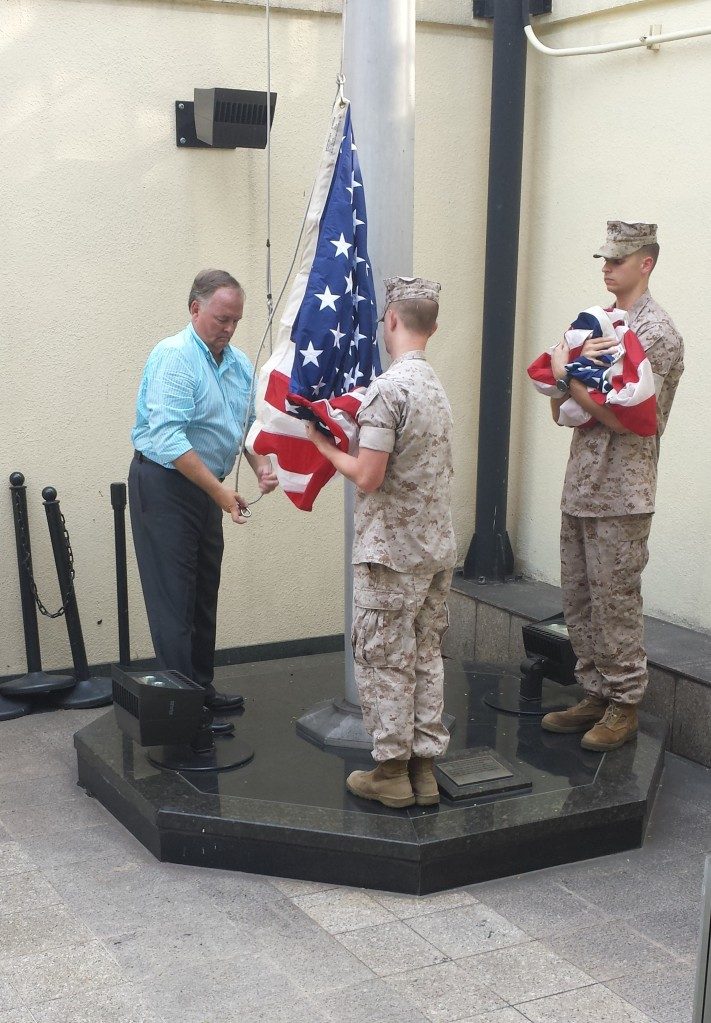 Randy Smith (L) brings down the flag at the American Consulate in Saigon for the second time during a recent trip to Vietnam to celebrate US Marine corps birthday November 10. Photo provided