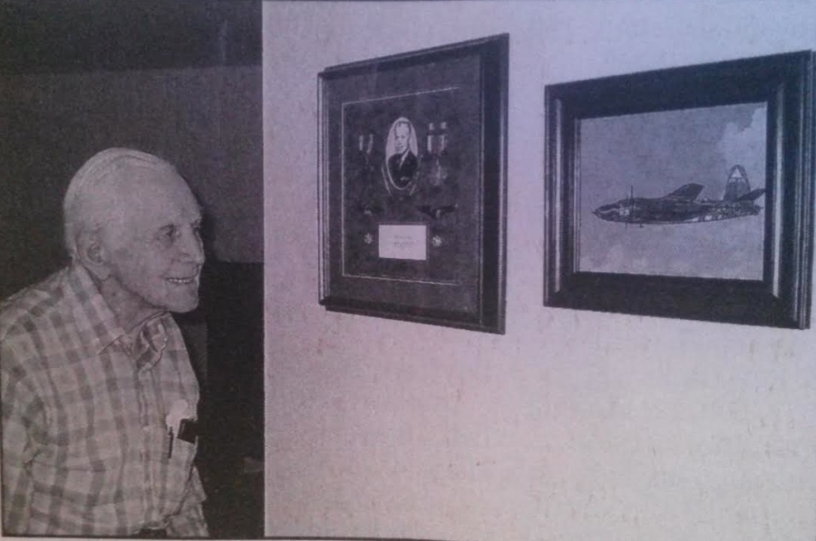 "John Nemeth of Port Charlotte looks at pictures on the wall of his home of his medals and the B-26 ""Marauder"" bomber he flew in World War II. Sun photo by Don Moore"