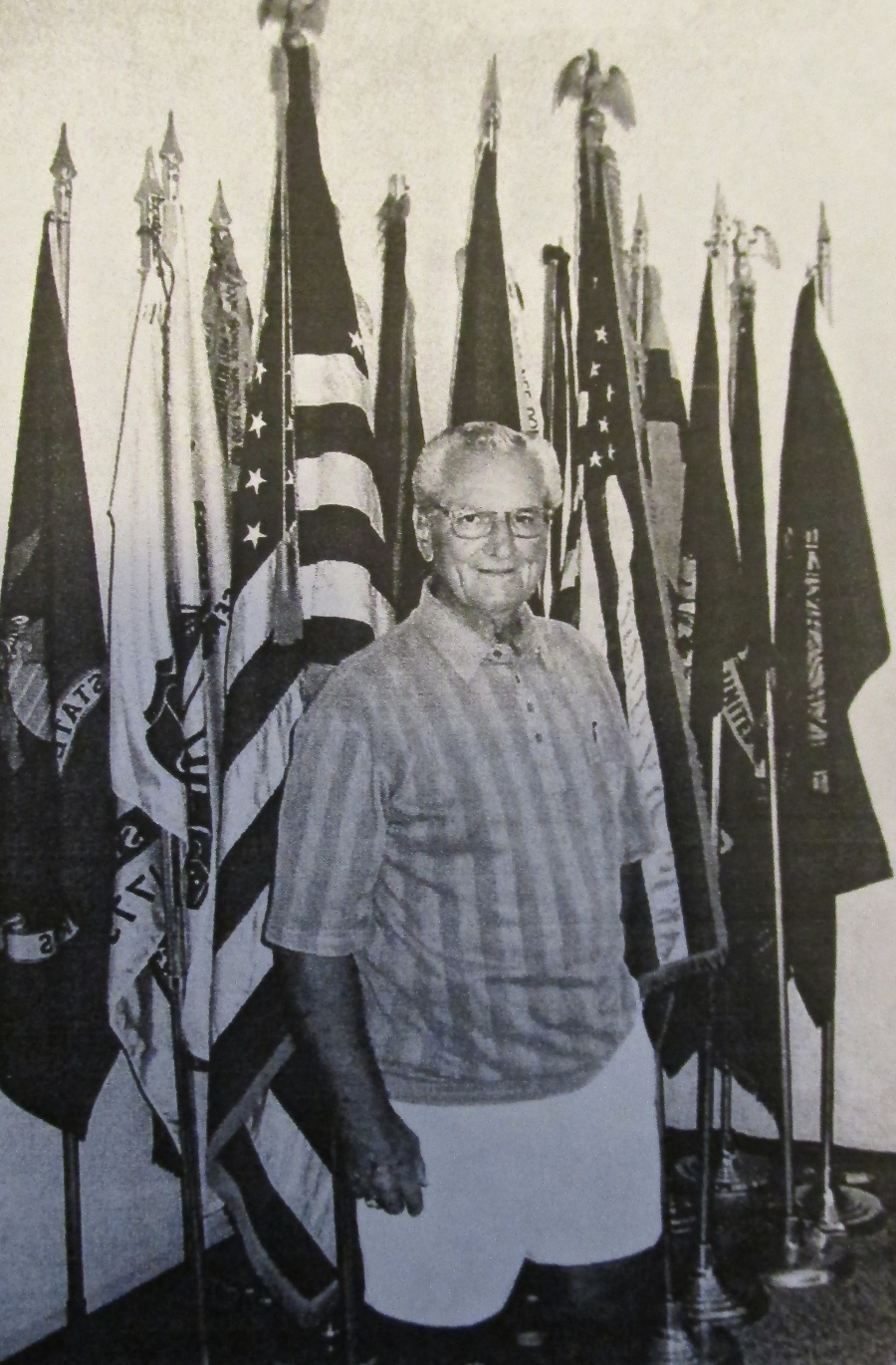Jerry Meadows of Port Charlotte was a staff sergeant in the 106th Infantry Division. He was wounded and captured at St. Vicht, Belgium, during the Battle of the Bulge in World War II. He stands before  the flags at American Legion Post 110 of Port Charlotte's temporary headquarters, where he's post commander. Sun photo by Don Moore