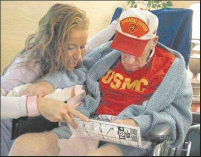 Helping out: Tara Turner, assistant director of nursing at Deep Creek Rehab & Nursing in Port Charlotte, Fla. helps Ray Richards, who fought with the 3rd Marine Division at Iwo Jima during World War II, tell his story with the use of a letter board, one letter at a time. Sun photo by Don Moore