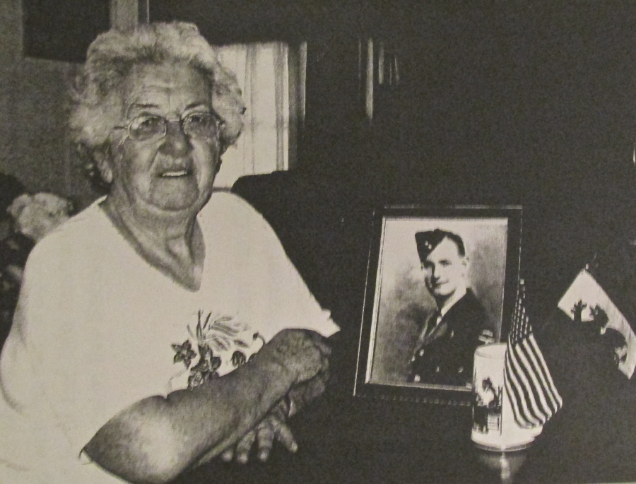 Elizabeth Adams of Harbor Cove in North Port was a WAAF in World War II. She installed radar in British Halifax bombers. She became an American citizen some years ago and keeps the small American flag to reminder her of the occasion. The Welsh flag with its red dragon reminds her of her homeland. The picture is of her late husband, Wing Cmdr. Allan Adams, a member of the Royal Canadian Air Force in the Second World War. Sun photo by Don Moore
