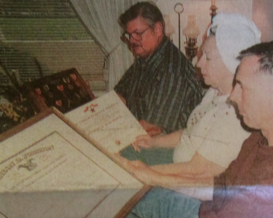 Left, Tim Kelly, Everett Driggers' stepson in the foreground, holds his dad's proclamation that notes he was the postmaster at Laurel beginning in 1965. Henrietta Driggers, his wife, looks at his Bronze Star commendation, and Charles Driggers, one of his three sons, holds a shadow box with all of his war medals. Sun photo by Don Moore