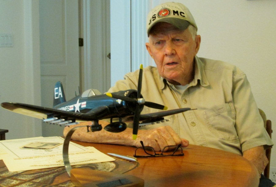 Peterson tells his story at 86 at his home in Englewood. In front of him is a model of a Corsair fighter like the ones he kept flying while serving as a Marine aviation mechanic between the Second World War and the Korean conflict. Sun photo by Don Moore