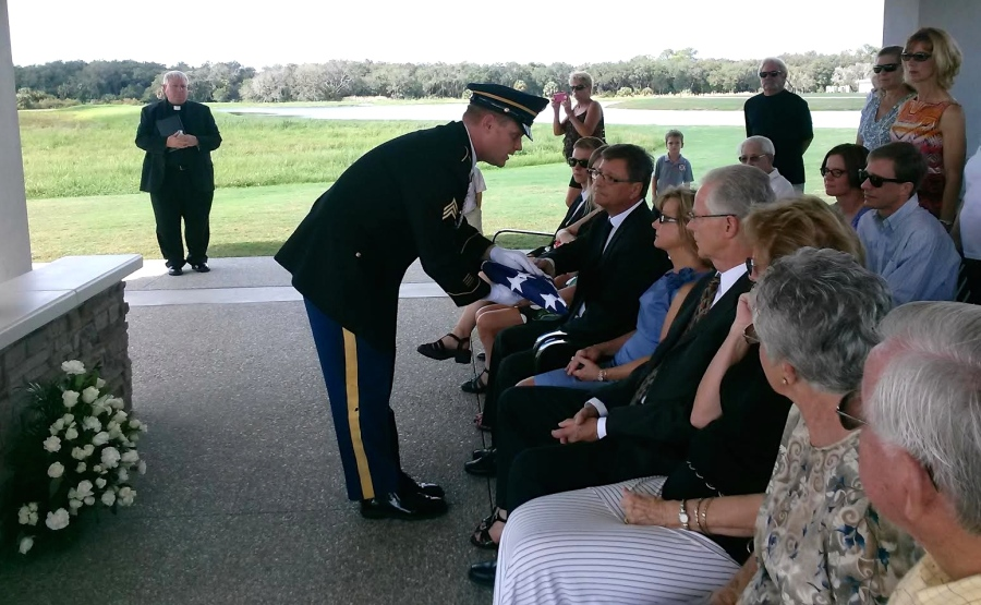The corporal commanding the three-man honor guard at the Monday funeral of former Army Sgt. Walter Tatko of Venice at Sarasota National Cemetery present his son, Stanley, with his burial flag. In the foreground Leonard Tatko, the soldier's younger brother, and other family members. Sun photo by Mary Auenson