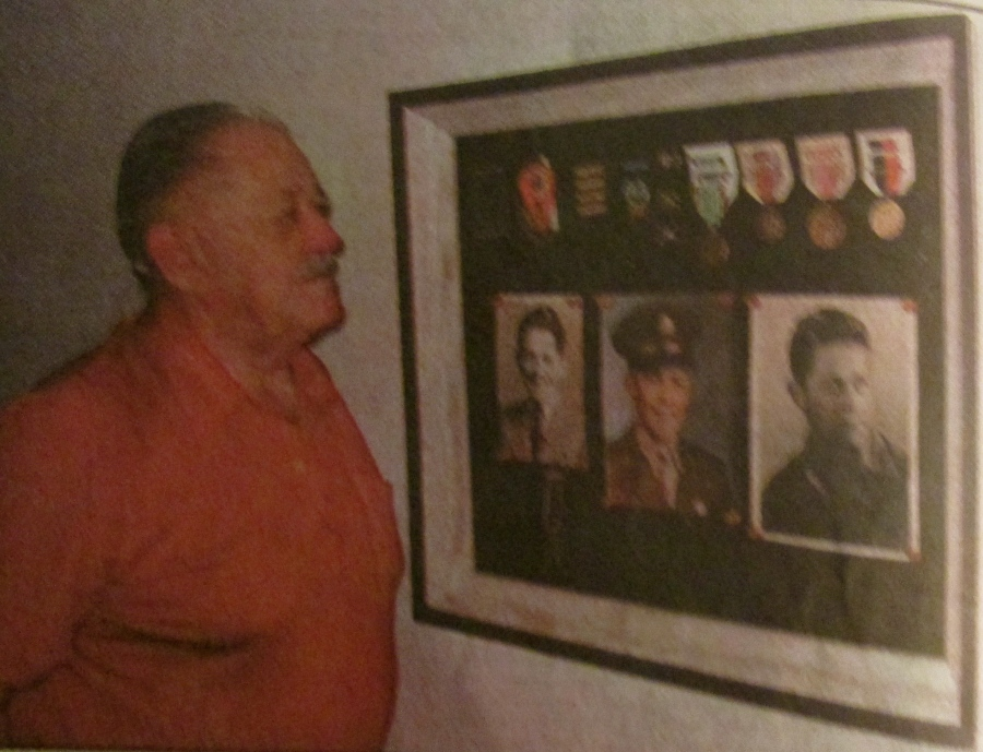Al Meersman of Port Charlotte, Fla. looks at pictures of himself and medals he received for serving in an anti-aircraft artillery unit with the 1st Army in Europe during World War II. His commendations include five battle stars for serving five major campaigns: Normandy, Northern France, Ardennes, Rhineland and Central Europe. The European Theater of Operations Ribbon, Good Conduct Medal and the World War II Victory Medal. Sun photo by Don Moore