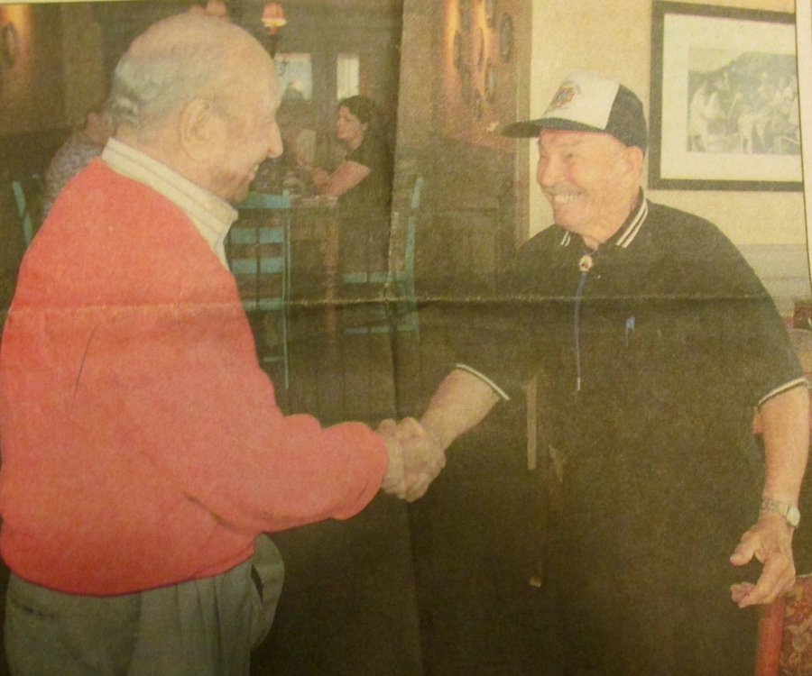 Capt. Walter Anstey of Venice (left) shakes hands with Sgt. Glenn Fackler of Punta Gorda, Fla. during their first meeting in 56 years. The two old soldiers , who met for lunch at the Olive Garden in Murdock, were members of the 7th Armored Division that distinguished itself at St. Vith during the Battle of the Bulge in World War II. Sun photo by Jonathan Fredin