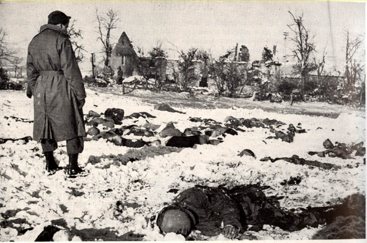 "A G.I. looks at the bodies of some of the 84 dead American soldiers slaughtered at Malmedy, Belgium by a German SS Panzer unit during the opening days of ""The Battle of the Bulge."" U.S. Army photo"