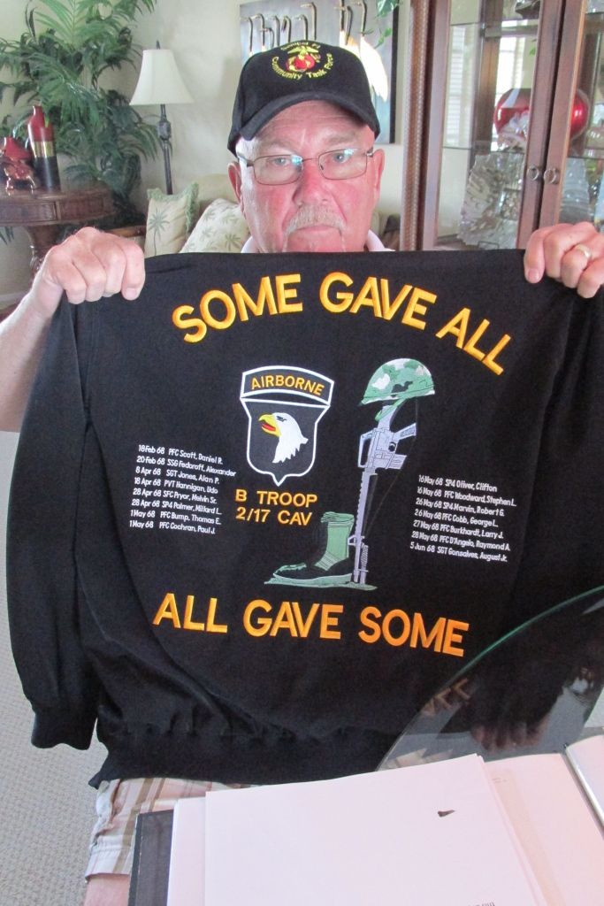 McConnell holds up his Vietnam jacket that expresses his sentiments. It also lists the names of the 15 soldiers in his squad lost in the fighting there who served with him. Sun photo by Don Moore