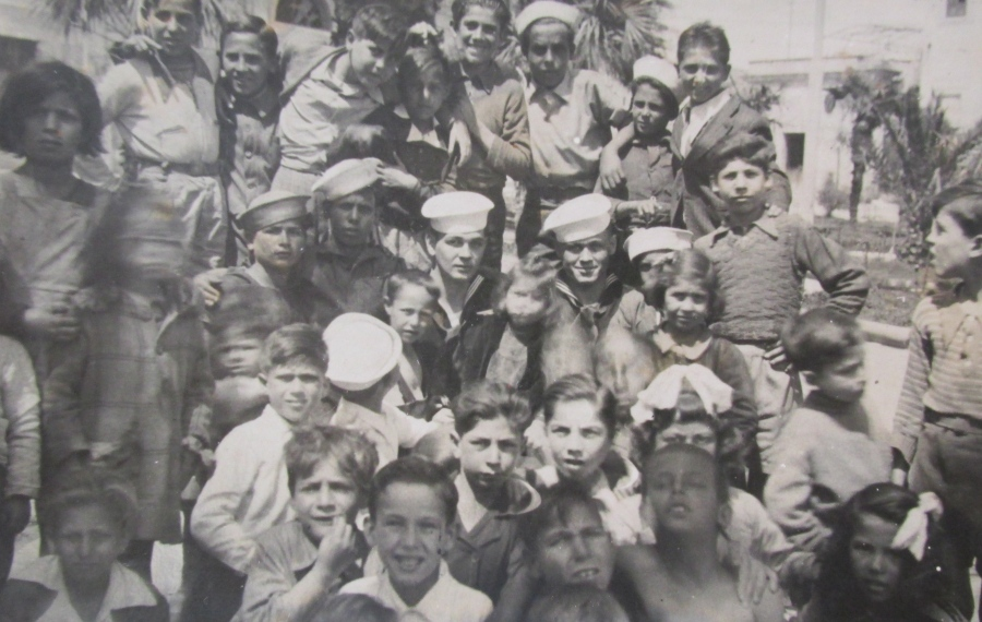 Murdock in the center with his white sailor hat and another buddy, to his left in uniform, surrounded by scores of kids on the Island of Sicily during the war. The two sailors were on shore leave. Photo provided.