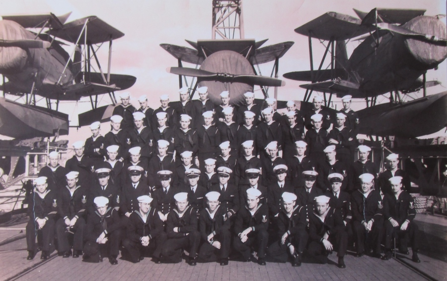 The engine-room crew of the USS Philadelphia on its fantail during the Second World War. Note the three covered patrol planes with wings folded flanking the group. Photo provided
