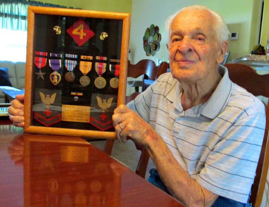 Bizeur holds a shadowbox of his World War II medals at his home in North Port. He received a Purple Heart, Bronze Star, Asiatic-Pacific Theatre Medal with three bronze battle starts, a Presidential Unit Citation, American Theater Medal, Occupation of Japan Medal and World War II Victory Medal. Sun photo by Do Moore