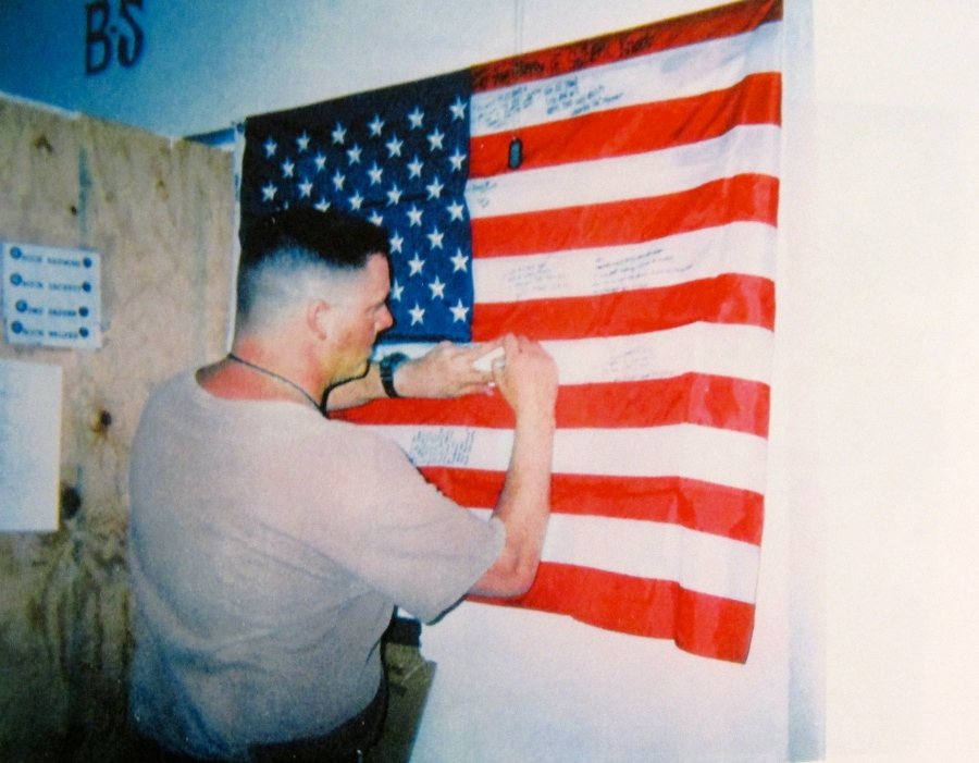 A Seabee signs an American flag for a fellow Seabee killed by an insurgent mortar round that was fired indiscriminately into Camp Falugah last September. The flag was being signed by many of the members of the dead Seabee's construction battalion. It was sent home to his parents. Photo by David Frey