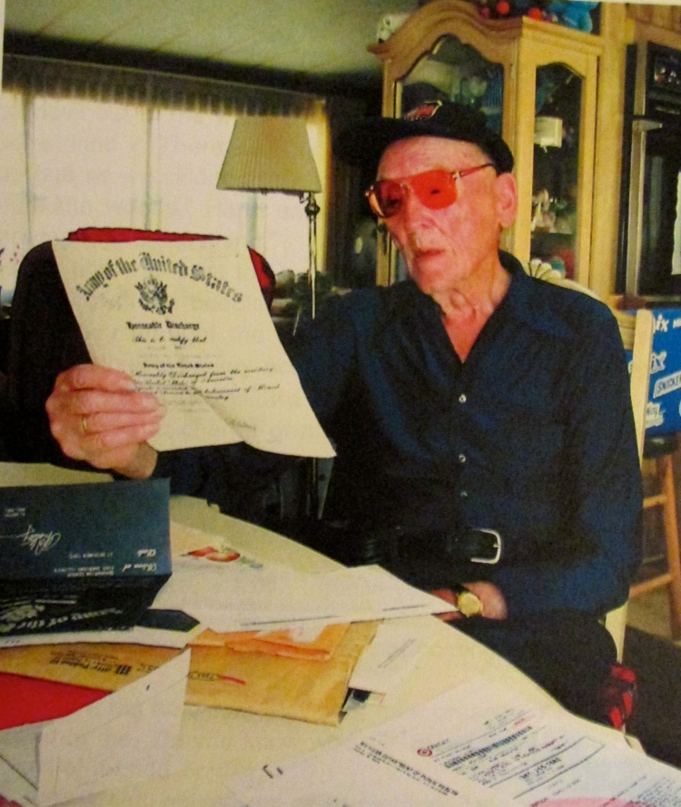 Roland Hardt, of El Jobean, looks at his Honorable Discharge that notes he received a Purple Heart, the Belgium Medal of Honor and five bronze Battle Stars for five major battles: Normandy, the Ardennes, North France, Rhineland and the Philippine Liberation Ribbon. Sun photo by Don Moore