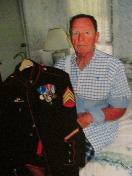 "Sgt. Jim Foster of Blue Heron Pines mobile home park holds his Marin dress uniform. He is a member of ""The Chosin Few,"" who fought with the 1st Marine Division in Korea. Sun photo by Don Moore"