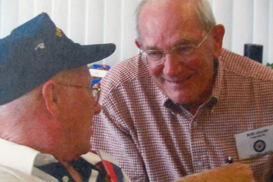 Adams talks with his best Navy buddy, Bob O'Brian, wearing his blue ball cap more than 50 years after they first met aboard the USS Libra during the Korean War. Photo provided
