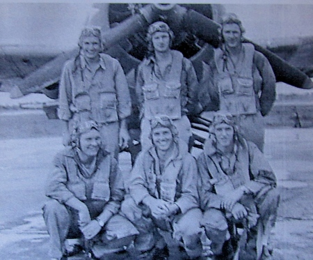 Lt. Schil, standing center, is pictured with his students at Sanford Naval Base after he returned from Guadalcanal. The fighter plane in the background is a Grumman F4F Wildcat. Photo provided