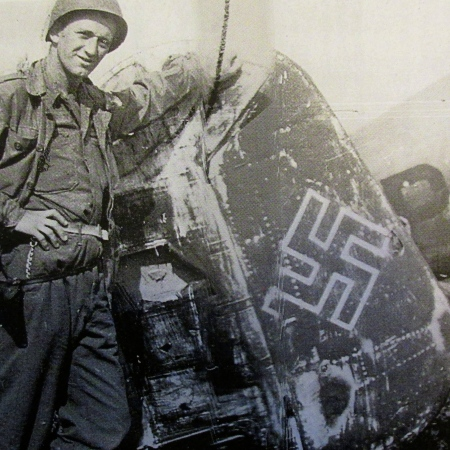 Sgt. Otto Brauer of Venice, Fla. stands beside the tale section of a downed German twin-engine bomber in northern France. He served as part of Gen. George Patton's 3rd Army in World War II. Photo provided