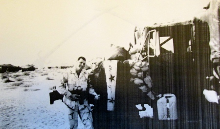 Sgt. Chris Grilo holds an M-16 assault rifle while standing beside his army truck draped with a captured enemy flag on the main road from Kuwait to Baghdad during the opening days of the Second Gulf War. His parents Mario and Phyllis Grilo live in Port Charlotte, Fla. Photo Provided