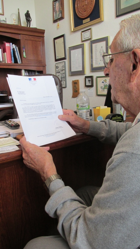 "Art Nicholas of Oak Forrest subdivision in Englewood looks at a letter from the Council General of France telling him he will be made a ""Knight in the Legion of Honor"" for his military service in France while serving in the Navy during World War II. Sun photo by Don Moore"