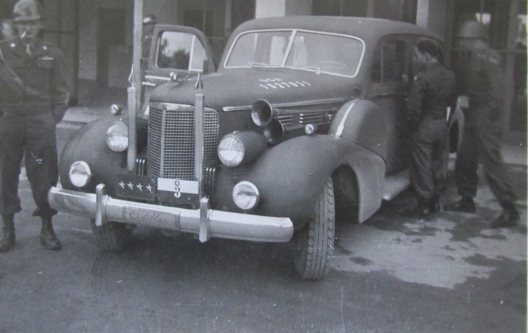 This is Patton's 1938 Cadillac staff car parked on a street in Nuremberg. Note the tag on the front with Patton's four star rank on the plate. Photo provided