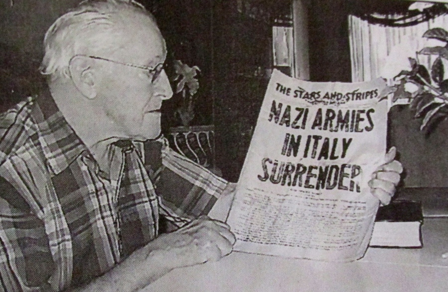 Former Sgt. Jay Vredevoogd of Port Charlotte, Fla. looks at the front page of 'Stars and Strips' for May 3, 1945 that proclaims: 'Nazi Armies in Italy Surrender.' He fought in Italy during the war. Sun photo by Don Moore