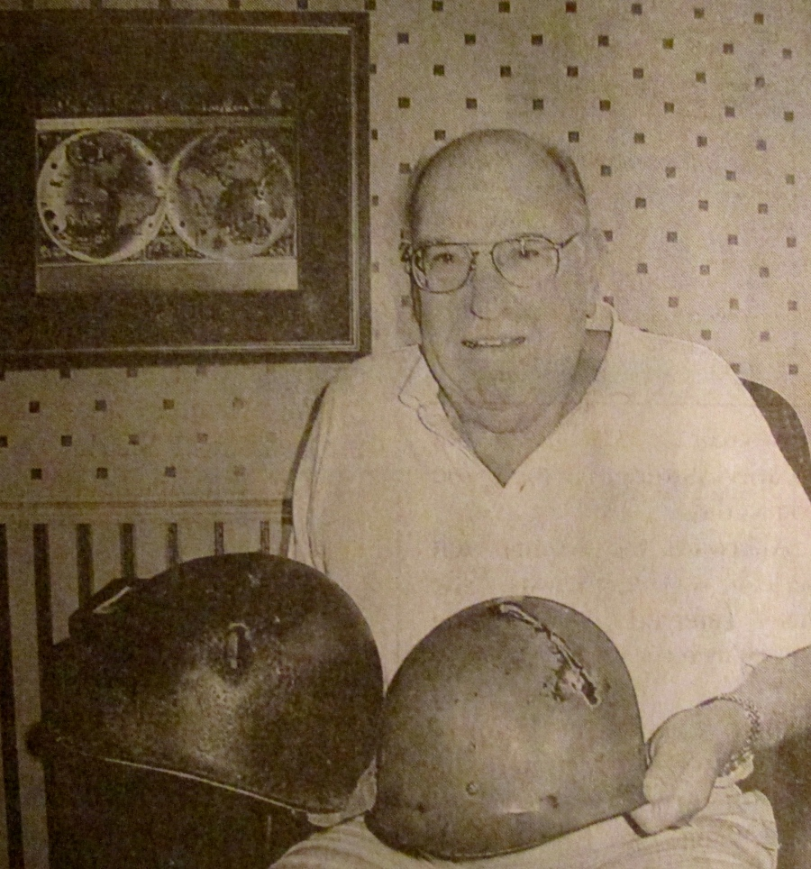 """Herb Brough of North Port, Fla. smiles as he holds his steel pot and helmet liner from World War II. He was hospitalized for months after being hit in the head with a piece of shrapnel during """"The Battle of the Bulge. Sun photo by Don Moore"""