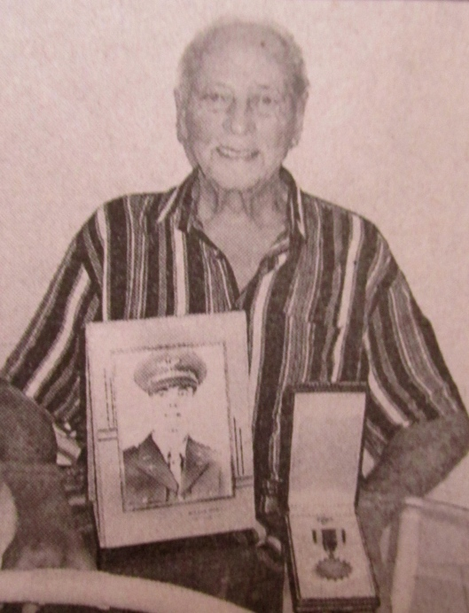 Paton talks about his World War II adventures. He is pictured with the Air Medal he received for 10 hazardous secret night missions and a picture of himself as an air cadet. Sun photo by Don Moore