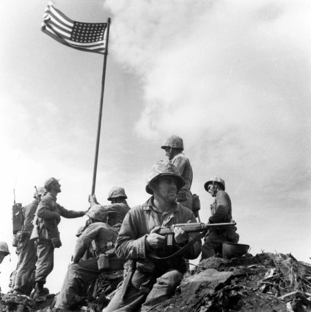 "This is the first flag-raising on Iwo Jima during World War II that most people it the U.S. know little or nothing about. This flag went up at 10:30 a.m. Feb. 23, 1945. The picture was taken by Marine Sgt. Lou Lowrey for ""Leatherneck"" magazine. It was suppressed by the Associated Press and wasn't run until after the war. Photo provided by Dick Honyak"