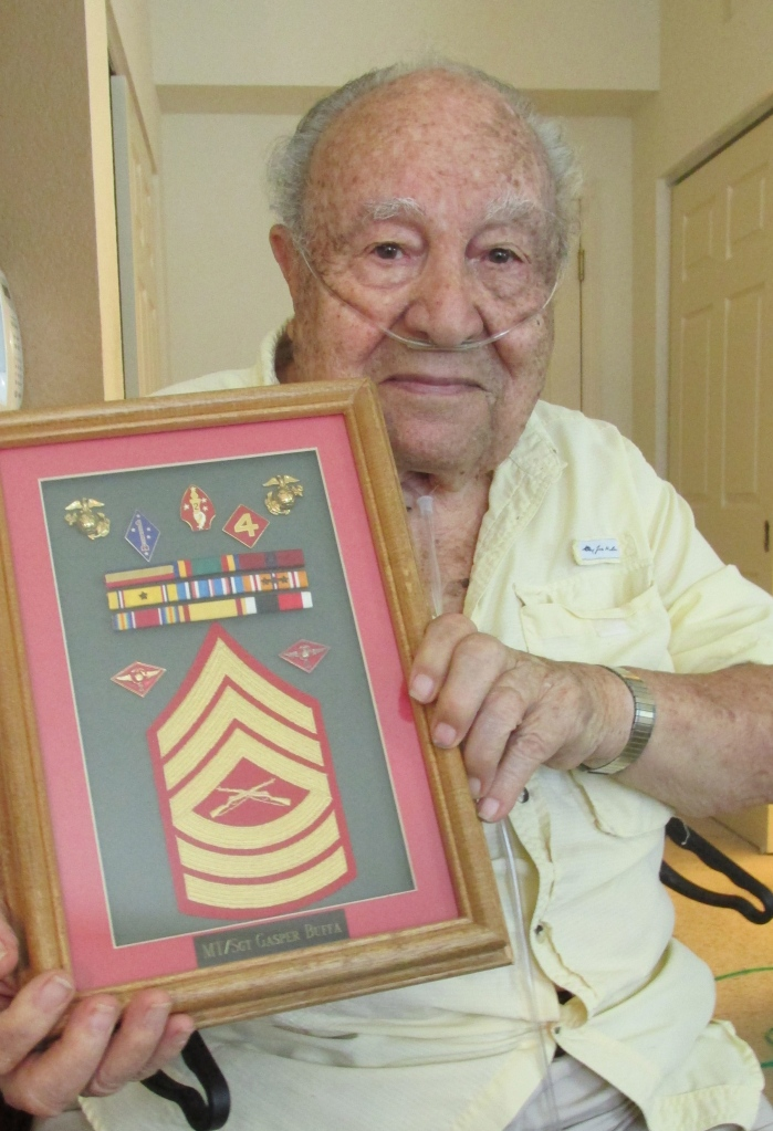 Buffa in June 2014 at 94 holding a shadowbox of his sergeant stripes and medals he received while serving in World War II. Sun photo by Don Moore