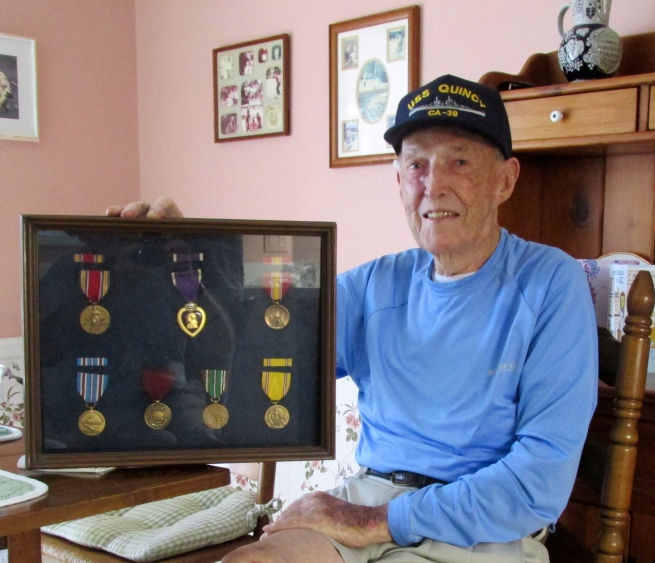 Cahill with a shadow box of World War II medals he received for his service during the Second Wold War. Sun photo by Don Moore