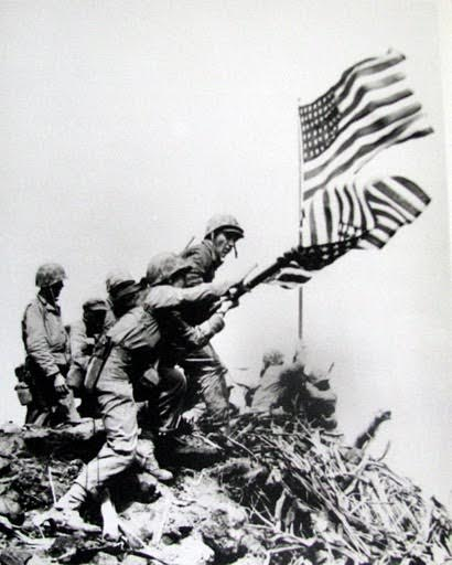 Marines put up the second American flag atop Mount Suribachi and take down the first flag on Feb. 23, 1945 during the Battle of Iwo Jima near the end of World War II. Photo provided by Dick Honyak