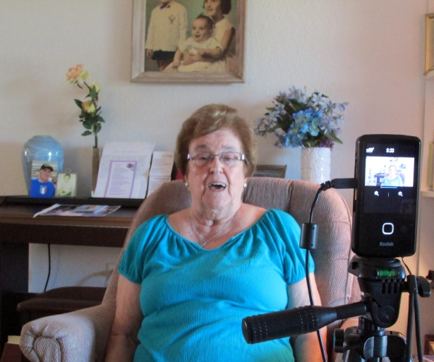 Katherine Riposta tells husband's war story during a DVD filming in her Deep Creek apartment. Frank is in the blue urn in the background on the piano to the left of her. Sun photo by Don Moore
