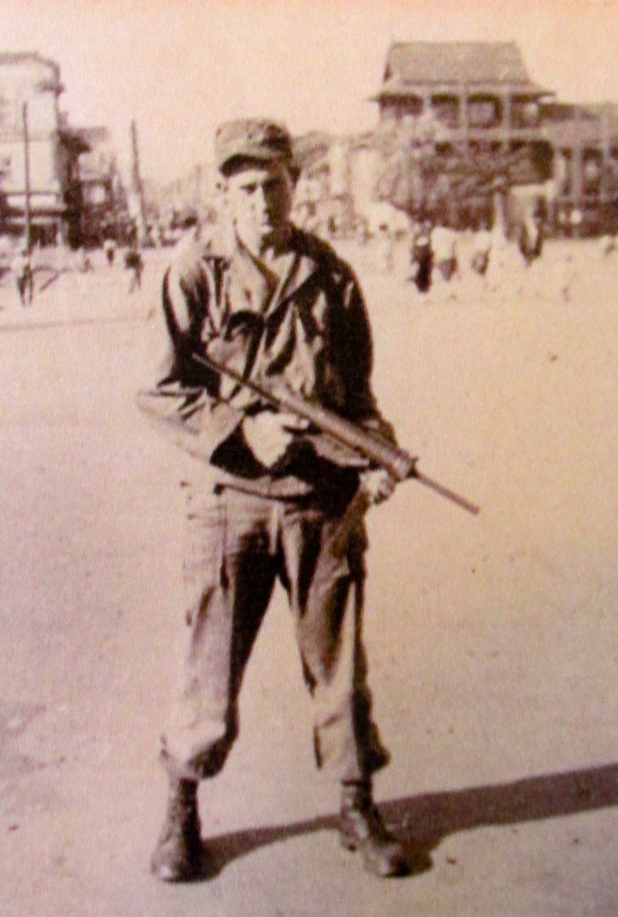 "Hilton holds a ""grease-gun,"" a .45 caliber sub-machine gun, while serving in Japan after World War. He never fired a shotin anger during war. Photo provided"