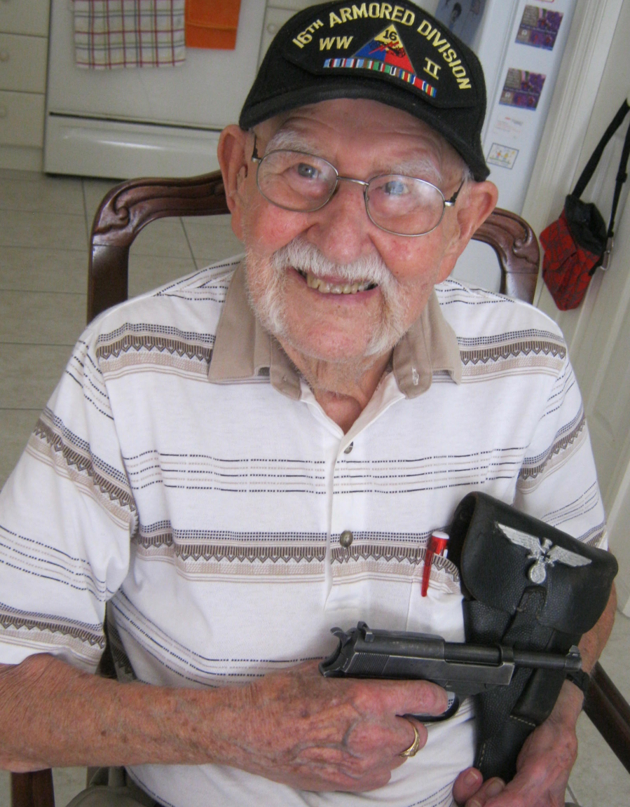 John Busse holds a German Walther P-38 pistol and holster he took off a Welmaracht officer he captured. The 9mm pistol is his favorite war souvenir. Sun photo by Mary Auenson