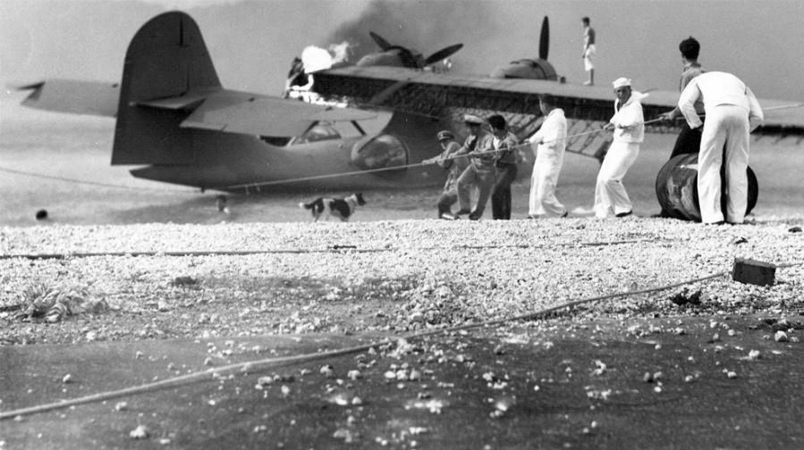 Sailors try and salvage a burning Catalina flying boat at the Ford Island Navy Base at Pearl Harbor. Most of the American aircraft at the field were descimated by the Japanese attack that launched the United States into World War II. U.S. Government photo