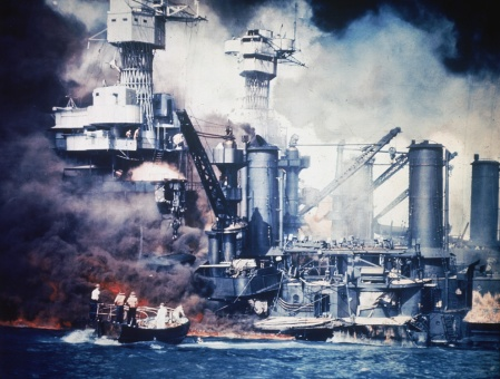 A Navy whale boat picks up a sailor swimming in Pearl Harbor in front of the battleship USS West Virginia badly damaged and in flames in the background on Dec. 7, 1941 shortly after the Japanese attacked Pearl Harbor.  U.S. Government photo